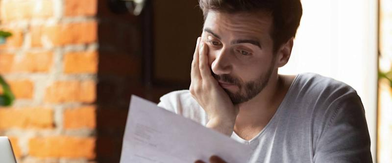 Confused frustrated young man reading mortgage rejection letter in cafe,