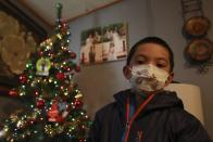 Angel, 6, poses in front of a Christmas tree at his home on Wednesday, Dec. 23, 2020, in Santa Fe, N.M. Angel's parents, both cooks, struggled to pay rent this year as their hours were cut in half. As immigrants in the country without work permission, they're ineligible for state unemployment or federal stimulus money. (AP Photo/Cedar Attanasio)
