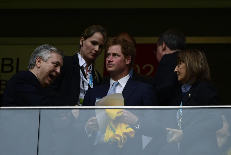 Prince Harry (centre) holds a Brazil jersey as he waits for the start of the match between Brazil and Cameroon at the Mane Garrincha National Stadium in Brasilia on June 23, 2014 (AFP Photo/Pierre-Philippe Marcou)