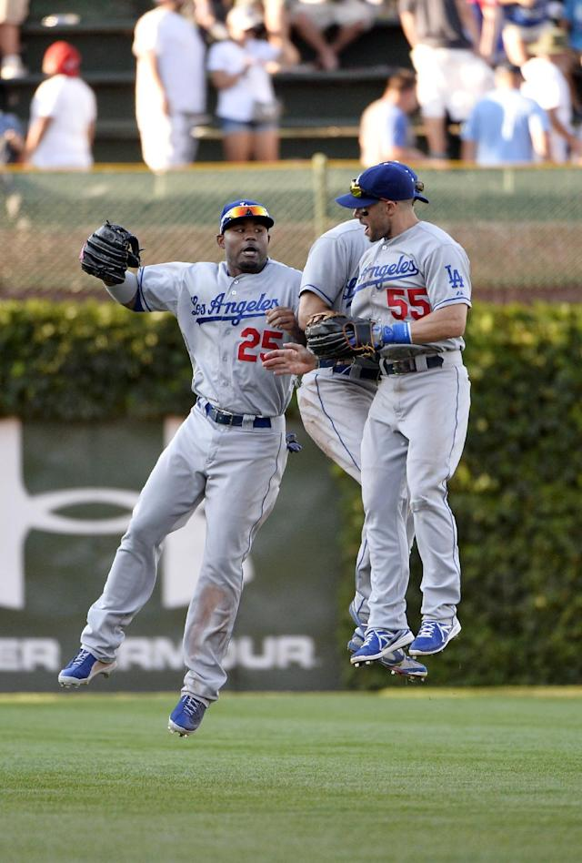 Los Angeles Dodgers outfielders Carl Crawford, left to right, Andre Ethier and Skip Schumaker celebrate their win after a baseball game against the Chicago Cubs, Saturday, Aug. 3, 2013, in Chicago. The Dodgers won 3-0. (AP Photo/Brian Kersey)