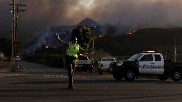 PHOTO: A police officer mans a checkpoint in front of an advancing wildfire Thursday, Nov. 8, 2018, near Newbury Park, Calif. (Marcio Jose Sanchez/AP)