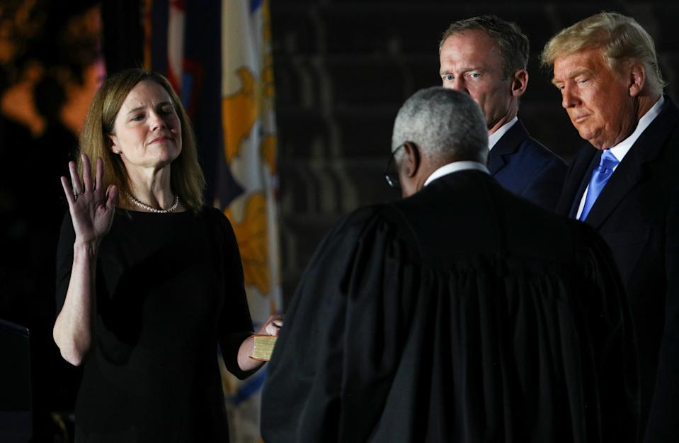 Judge Amy Coney Barrett is sworn in as an associate justice of the U.S. Supreme Court by Supreme Court Justice Clarence Thomas as her husband Jesse Barrett and President Donald Trump watch on the South Lawn of the White House in Washington, U.S., October 26, 2020.   REUTERS/Tom Brenner