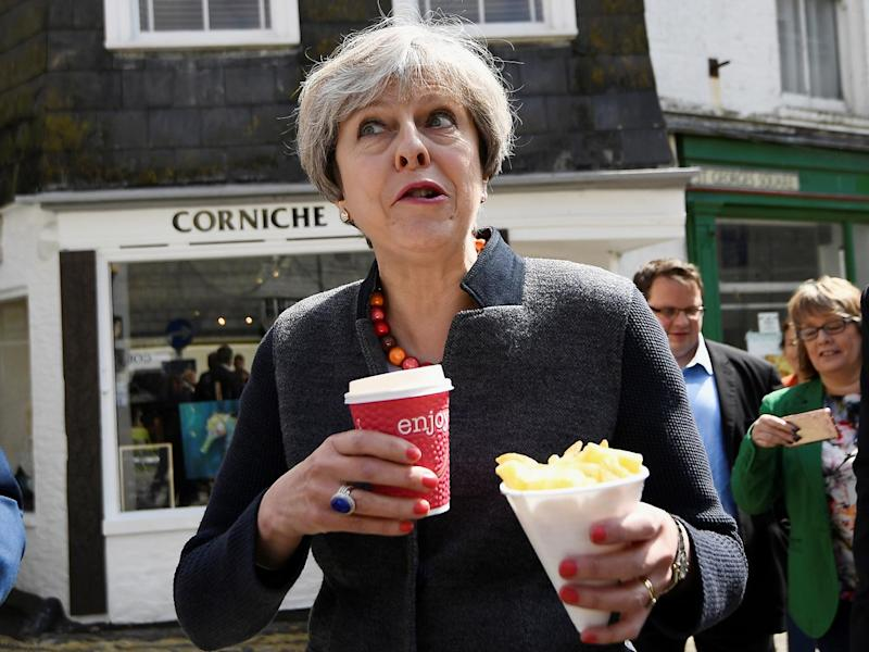 Britain's Prime Minister Theresa May enjoys some chips during a campaign stop in Mevagissey, Cornwall (Reuters)