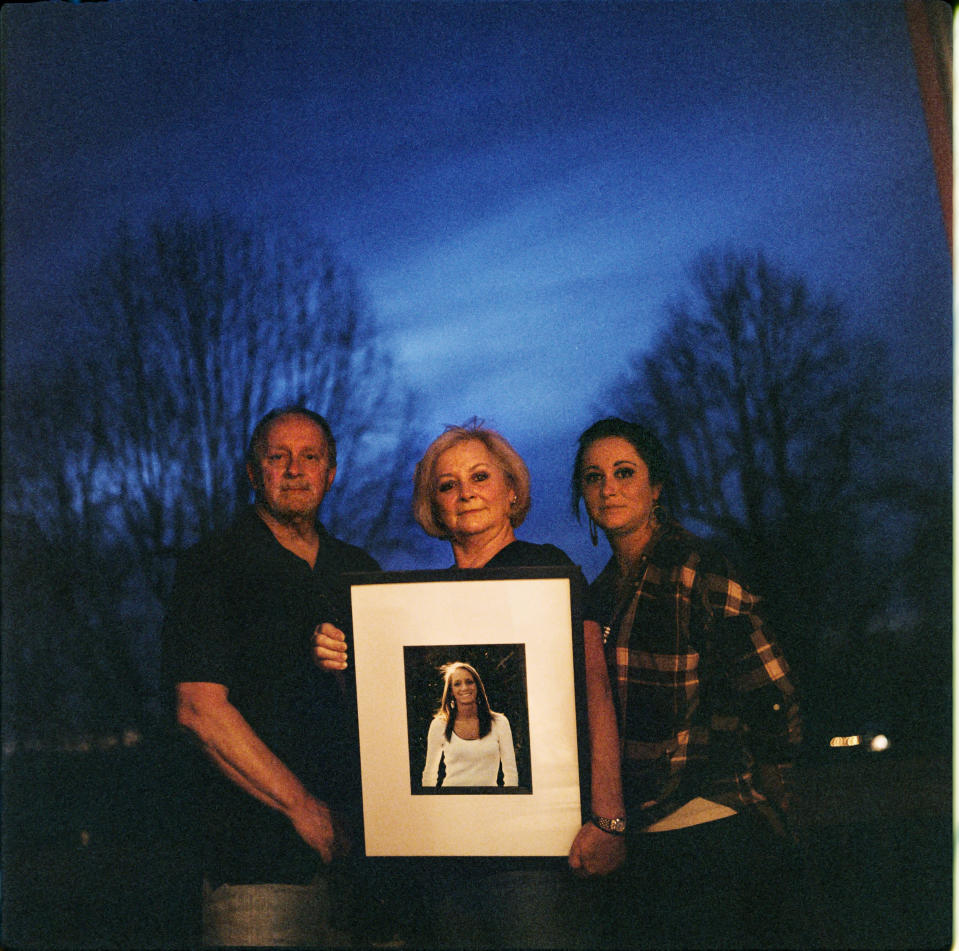 """In this photo made with a medium format film camera, Jeff and Lola Carter stand with their daughter, Amanda, and a framed photo of Kayla, their daughter who struggled with drug addiction, Thursday, March 18, 2021, at their home in Milton, W.Va., Kayla Carter grew up in a tiny town 20 miles from Huntington, in a house with a swimming pool in the backyard. She had a brilliant mind for math and loved the stars. Her family always thought she'd grow up to work for NASA. Instead, she was addicted to opioids by the time she turned 20. """"We went through living hell,"""" said Lola. Kayla was hospitalized in June with endocarditis, a heart infection common among injection drug users. It seemed like she was suddenly determined to live. In October, her mother couldn't reach her one Friday. She went to her apartment, and found her dead on her bathroom floor. They are still waiting for the medical examiner's report, but her father would rather never see it. It brings him comfort to think she died from a complication from her surgeries, and not that she relapsed and overdosed. Either way, the drugs killed her, he said. """"The only thing about any of it gives me any relief at all,"""" he says, """"is knowing we're not the only ones."""" (AP Photo/David Goldman)"""