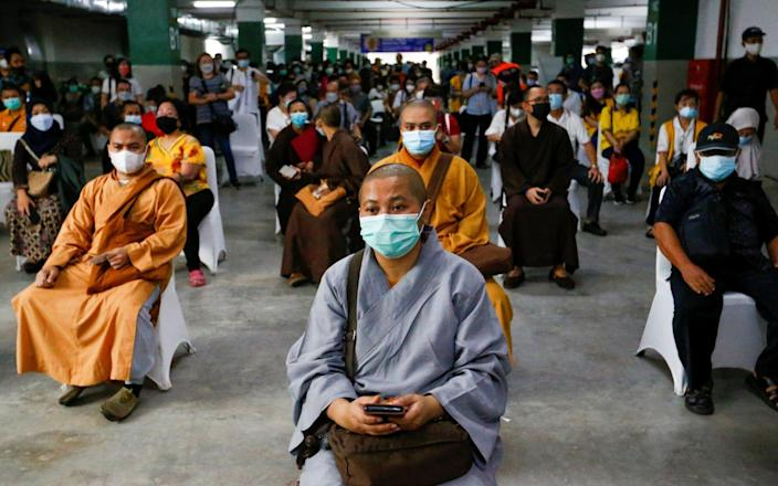 Indonesian monks wait to receive their first dose of China's Sinovac Biotech vaccine - Ajeng Dinar Ulfiana/Reuters