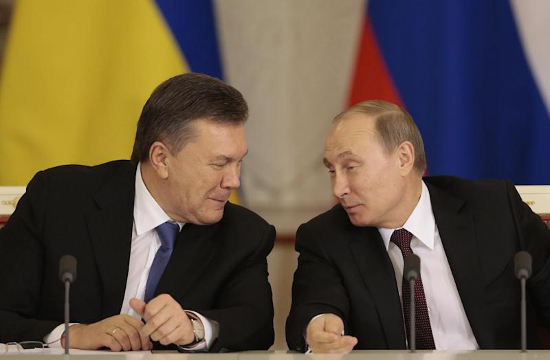 Russian President Vladimir Putin, right, and his Ukrainian counterpart Viktor Yanukovych share a joke during a news conference after their meeting in Moscow on Tuesday, Dec. 17, 2013. (AP Photo/Ivan Sekretarev)