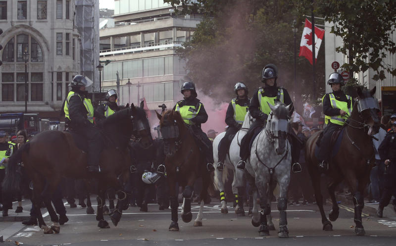 Mounted police horses react to a flare going off during an anti-fascist demonstration held in protest against a rival march by the Football Lads Alliance march, London, Saturday, Oct. 13, 2018. (AP Photo/Alastair Grant)