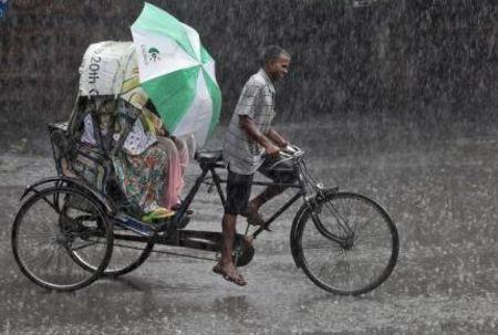 Commuters use an umbrella to protect themselves from a heavy rain shower as they travel in a cycle rickshaw in Chandigarh
