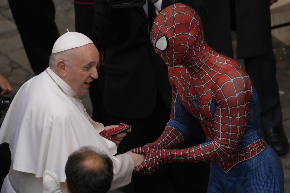 Pope Francis meets Spider-Man, who presents him with his mask, at the end of his weekly general audience with a limited number of faithful in the San Damaso Courtyard at the Vatican, Wednesday, June 23, 2021. The masked man works with sick children in hospitals. (AP Photo/Andrew Medichini)