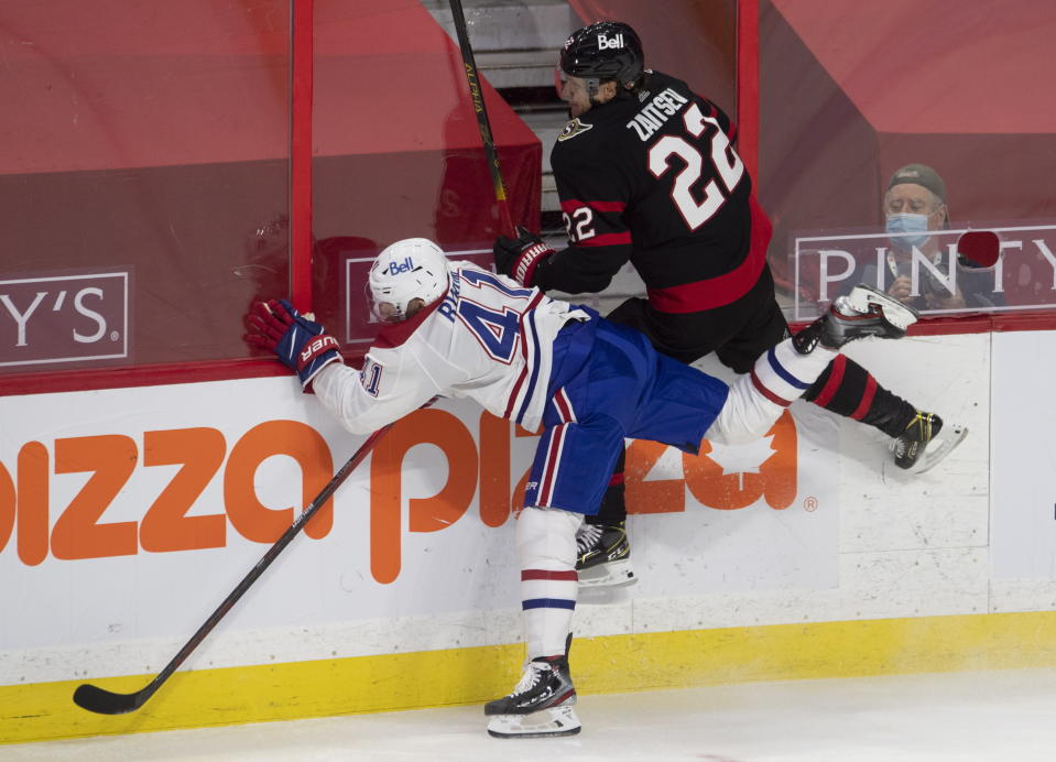 Ottawa Senators defenseman Nikita Zaitsev (22) and Montreal Canadiens left wing Paul Byron (41) collide along the boards during the second period of an NHL hockey game Sunday, Feb. 21, 2021, in Ottawa, Ontario. (Adrian Wyld/The Canadian Press via AP)