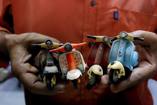 <p>A shopkeeper and Vespa enthusiast holds his collection of mini memorabilia, at his auto parts shop in Karachi, Pakistan Feb. 28, 2018. (Photo: Akhtar Soomro/Reuters) </p>