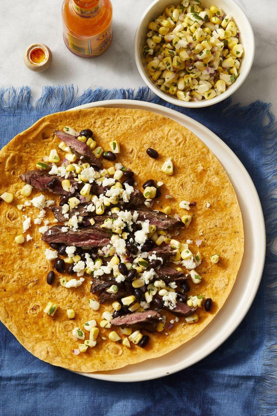 """<p>Looking for a new twist on Taco Tuesday? Swap out the taco shell for a delicious wrap, then fill up with sliced steak, corn, cilantro, black beans, and queso fresco.</p><p><em><a href=""""https://www.goodhousekeeping.com/food-recipes/a28223751/southwest-steak-wraps-recipe/"""" rel=""""nofollow noopener"""" target=""""_blank"""" data-ylk=""""slk:Get the recipe for Southwest Steak Wraps »"""" class=""""link rapid-noclick-resp"""">Get the recipe for Southwest Steak Wraps »</a></em></p>"""