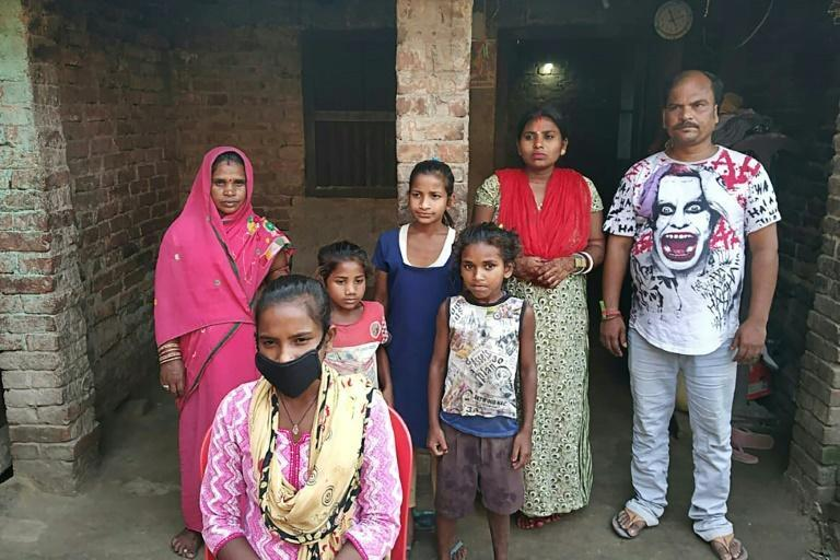 Jyoti Kumari Paswan, wearing a face mask, stands with her family outside their home in the northeastern state of Bihar (AFP Photo/STR)