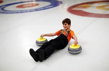"""A Yazidi refugee from Kurdistan laughs as he learns the sport of curling at the Royal Canadian Curling Club during an event put on by the """"Together Project"""", in Toronto, March 15, 2017.    REUTERS/Mark Blinch"""
