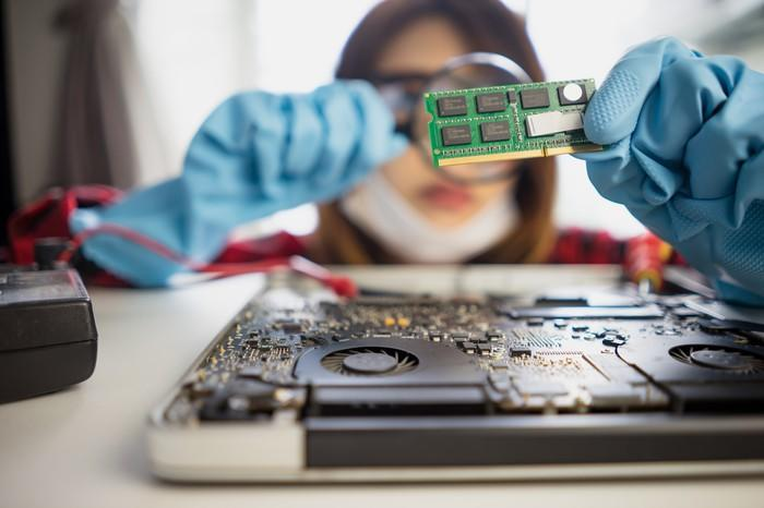 An Asian female worker with blue gloves inspects a memory card with a magnifying glass.