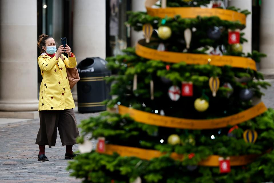A pedestrian wearing a face mask or covering due to the COVID-19 pandemic takes a photograph of Christmas trees in Covent Garden in central London on November 17, 2020. - Britain has been the worst-hit nation in Europe recording more than 50,000 coronavirus deaths from some 1.2 million positive cases. (Photo by Tolga Akmen / AFP) (Photo by TOLGA AKMEN/AFP via Getty Images)