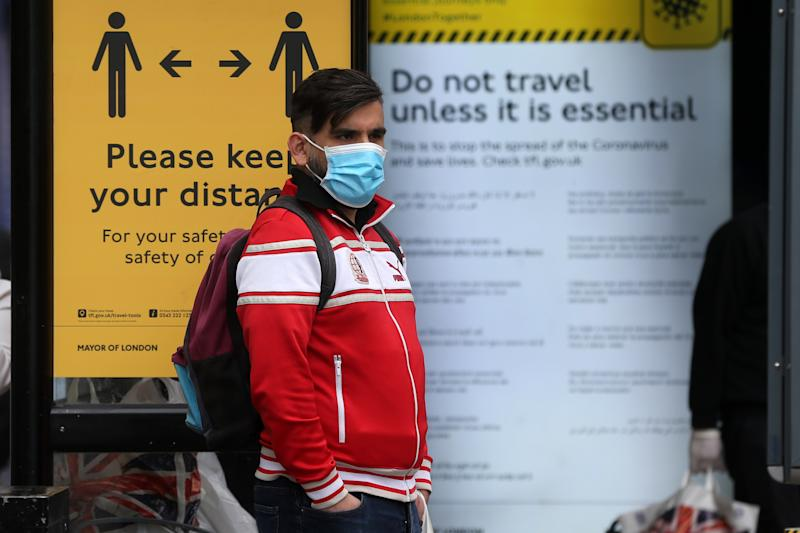 "A man wearing a protective face mask waits at a bus stop surrounded by information on social distancing in Camden in central London on May 11, 2020, as life in Britain continues during the nationwide lockdown due to the novel coronavirus pandemic. - British Prime Minister Boris Johnson on May 10 announced a phased plan to ease a nationwide coronavirus lockdown, with schools and shops to begin opening from June 1 -- as long as infection rates stay low. Starting this week, he said the government would be ""actively encouraging"" people to return to work where they could not do so from home, for example in manufacturing or construction. (Photo by ISABEL INFANTES / AFP) (Photo by ISABEL INFANTES/AFP via Getty Images)"