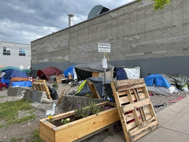 People living at a homeless camp at 231-233 George Street in Prince George, B.C., have been told they must leave by June 25 or face arrest. (Andrew Kurjata/CBC - image credit)