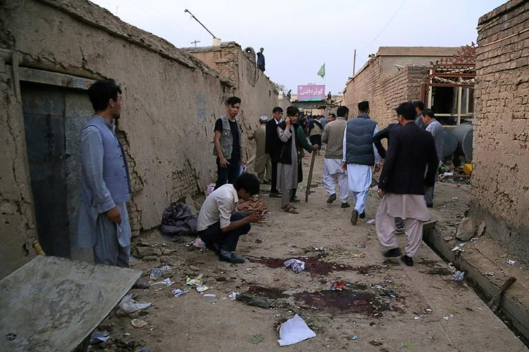Residents gather near an education centre in the Afghan capital Kabul after a suicide bomber struck, killing at least 18 people