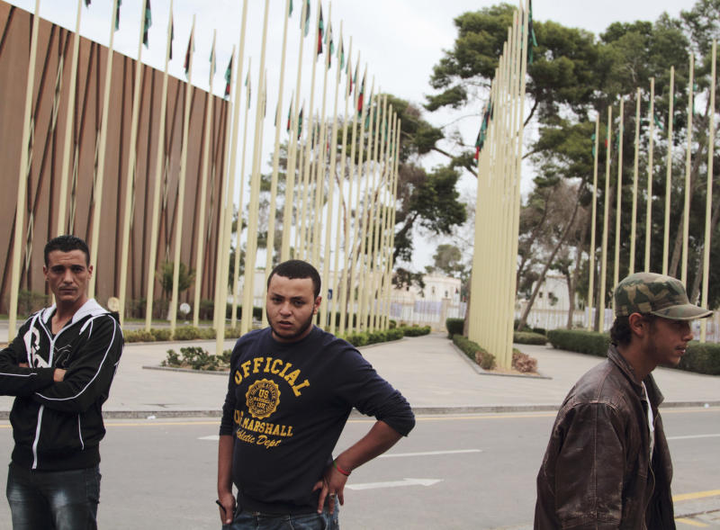 Young men representing ex-revolutionary militia groups, arriving from different towns in Libya, gather in front of the General National Congress (GNC) building in Tripoli, Libya, Thursday, Nov. 1, 2012. Since tuesday, armed protestors have cut the main road leading to the Parliament, vowing not to leave until members of the ousted regime of dictator Moammar Gadhafi are excluded from political life.  Five of the 27 ministers would be reconsidered, a spokesman said, after concerns were raised over their ties to the deposed regime. But that was not good enough for the protesters, who tried to storm the building but were turned back by security forces. (AP Photo/Gaia Anderson)