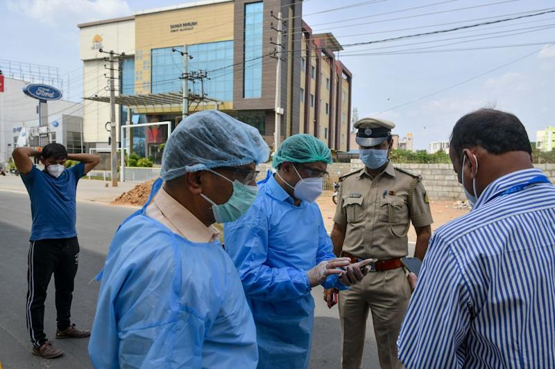 Paramedics and police officials in Bangalore, India, plan the evacuation of a suspected COVID-19 patient on March 25.