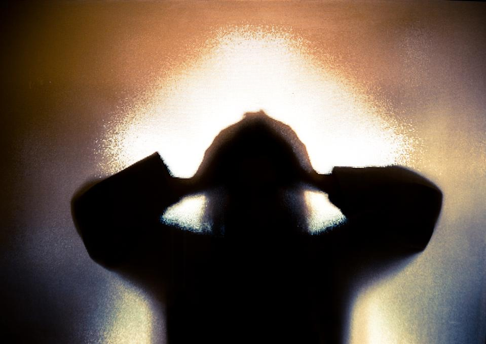 Colour backlit image of the silhouette of a woman with her hands on her head in a gesture of despair. The silhouette is distorted, and the arms elongated, giving an alien-like quality. The image is sinister and foreboding, with an element of horror. It is as if the 'woman' is trying to escape from behind the glass. Horizontal image with copy space.