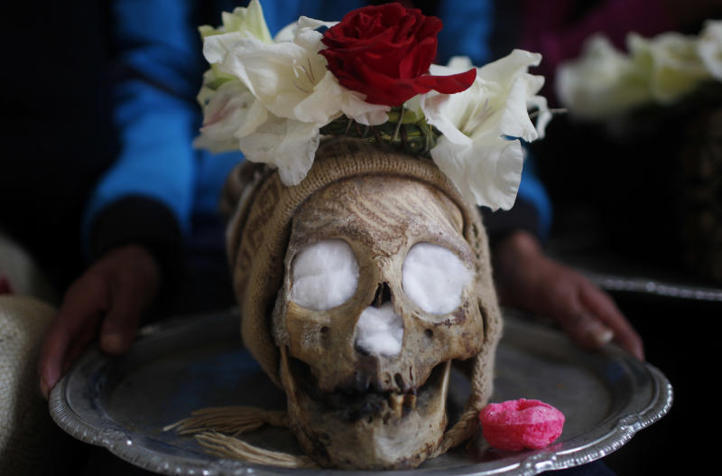 "A man carries a decorated human skull or ""natita"" on a silver-colored tray during the Natitas Festival at the Cementerio General, in La Paz, Bolivia, Friday, Nov. 8, 2013. Natitas are human skulls from unnamed, abandoned graves that are cared for and decorated by faithful who use them as amulets believing they serve as protection. According to tradition, the skull should belong to an unknown person, but in some cases are those of distant relatives. The devotees say they get the skulls from abandoned cemeteries.(AP Photo/Juan Karita)"