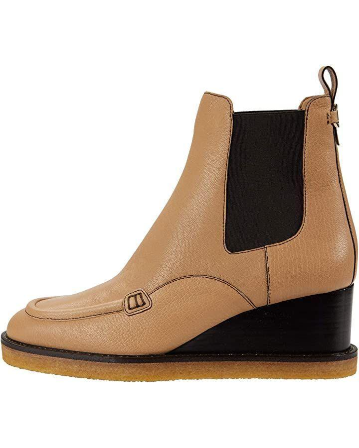"""<p><strong>Salvatore Ferragamo</strong></p><p>Zappos.com</p><p><strong>$995.00</strong></p><p><a href=""""https://go.redirectingat.com?id=74968X1596630&url=https%3A%2F%2Fwww.zappos.com%2Fa%2Fthe-style-room%2Fp%2Fsalvatore-ferragamo-ciminna-almond%2Fproduct%2F9412269%2Fcolor%2F25&sref=https%3A%2F%2Fwww.harpersbazaar.com%2Ffashion%2Fg34485018%2Fbest-wide-width-boots%2F"""" rel=""""nofollow noopener"""" target=""""_blank"""" data-ylk=""""slk:Shop Now"""" class=""""link rapid-noclick-resp"""">Shop Now</a></p><p>This buttery-leather wedge bootie is comfortable, chic, and sizes up to a C width. </p>"""