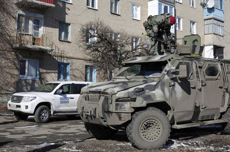 A Ukrainian serviceman stands on top of a KRAZ armoured vehicle close to a car of the Organization for Security and Cooperation in Europe (OSCE) in Soledar, Donetsk region, on February 17, 2015