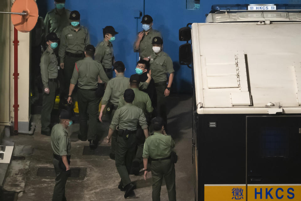 Joshua Wong, center right, one of the 47 pro-democracy Hong Kong activists, is escorted by Correctional Services officers to prison in Hong Kong, early Tuesday, March 2, 2021. Hong Kong police on Monday brought 47 pro-democracy activists to court on charges of conspiracy to commit subversion under the national security law imposed on the city by Beijing last year. (AP Photo/Kin Cheung)