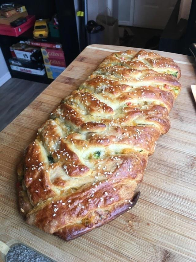 A braided bread with chicken and broccoli.