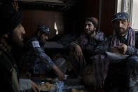 Taliban fighters, some wearing new police uniforms, eat lunch at a police station in Kabul, Afghanistan, Wednesday, Sept. 15, 2021. (AP Photo/Felipe Dana)