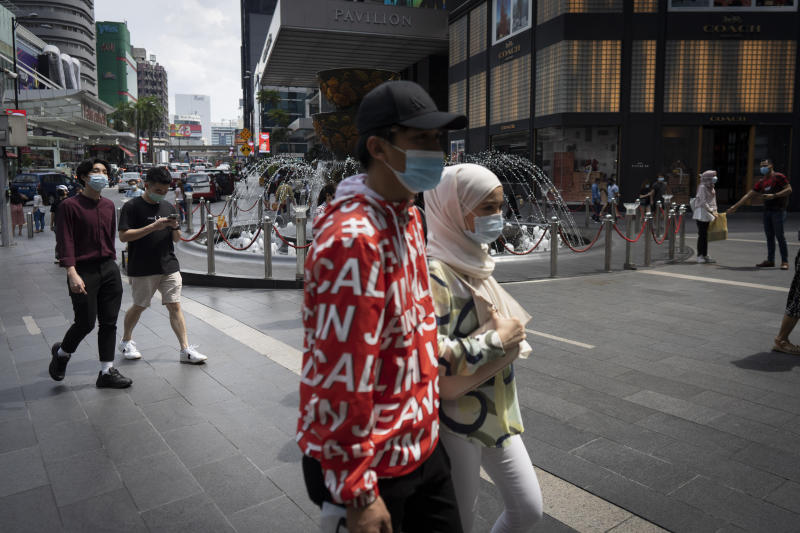 Shoppers wearing face mask walks at a shopping mall in downtown Kuala Lumpur, Malaysia, on Sunday, June 7, 2020. Malaysian government has lifted the conditional movement order (CMCO) and replaced it with a recovery movement control order effective June 10 until Aug. 31. (AP Photo/Vincent Thian)