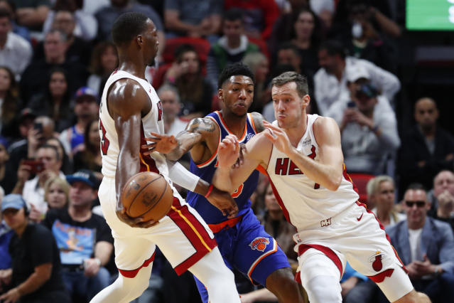 Miami Heat center Bam Adebayo, left, attempts to hand the ball off to guard Goran Dragic, right, as New York Knicks guard Elfrid Payton reaches for the ball during the first half of an NBA basketball game Friday, Dec. 20, 2019, in Miami. (AP Photo/Wilfredo Lee)