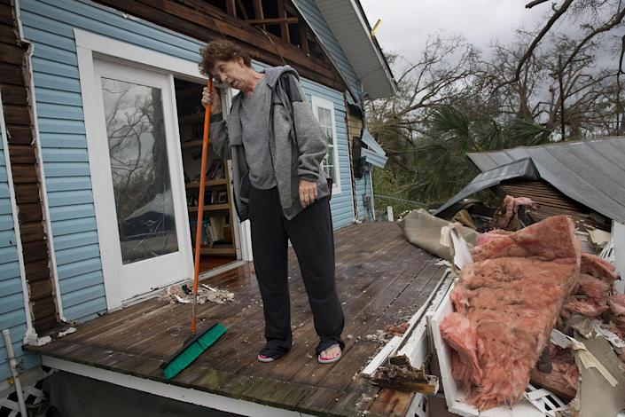<p>Phlomena Telker stands on what was her covered porch after hurricane Michael tore the roof of her home as it passed through the area on Oct. 10, 2018 in Panama City, Fla. (Photo: Joe Raedle/Getty Images) </p>