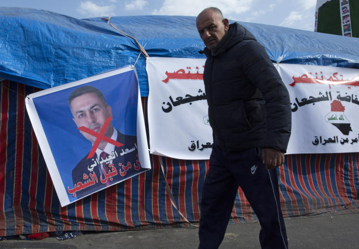 "A protester walks past a poster with a defaced picture of the governor of the southern Basra province Asaad al-Eidani and Arabic that reads ""rejected by the people,"" during the ongoing protests, in Tahrir square, in Baghdad, Iraq, Wednesday, Dec. 25, 2019. An Iranian-backed bloc in Iraq's parliament proposed al-Eidani as the country's next prime minister. However, the nomination was promptly rejected by Iraqi protesters who want an independent candidate to take over the government. Earlier on Wednesday, outgoing higher education minister, who had also been rejected by protesters on the streets, withdrew his nomination for prime minister. (AP Photo/Nasser Nasser)"