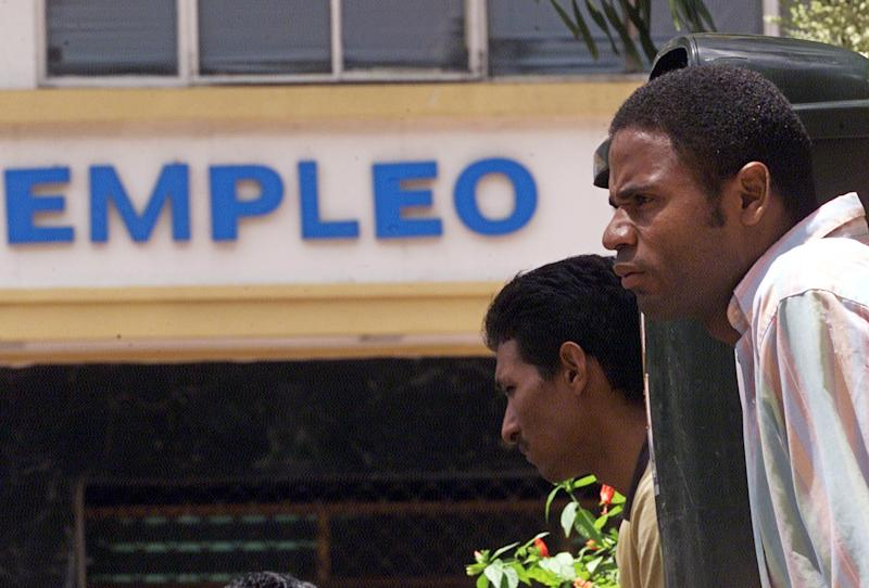 """Jhony Ferranco (R) waits with other unemployed Venezuelan workers outside a Labor Ministry office to hear about job prospects, in Caracas September 2, 2003. With their nation mired in a fierce recession, middle-class Venezuelans are struggling to stay afloat as unemployment, inflation and devaluation nudge them closer to the ranks of the poor. Sign reads """"work"""" (""""Empleo""""). Picture taken September 2, 2003. (Spelling of """"Jhony"""" is correct). REUTERS/Howard Yanes HY/HB"""