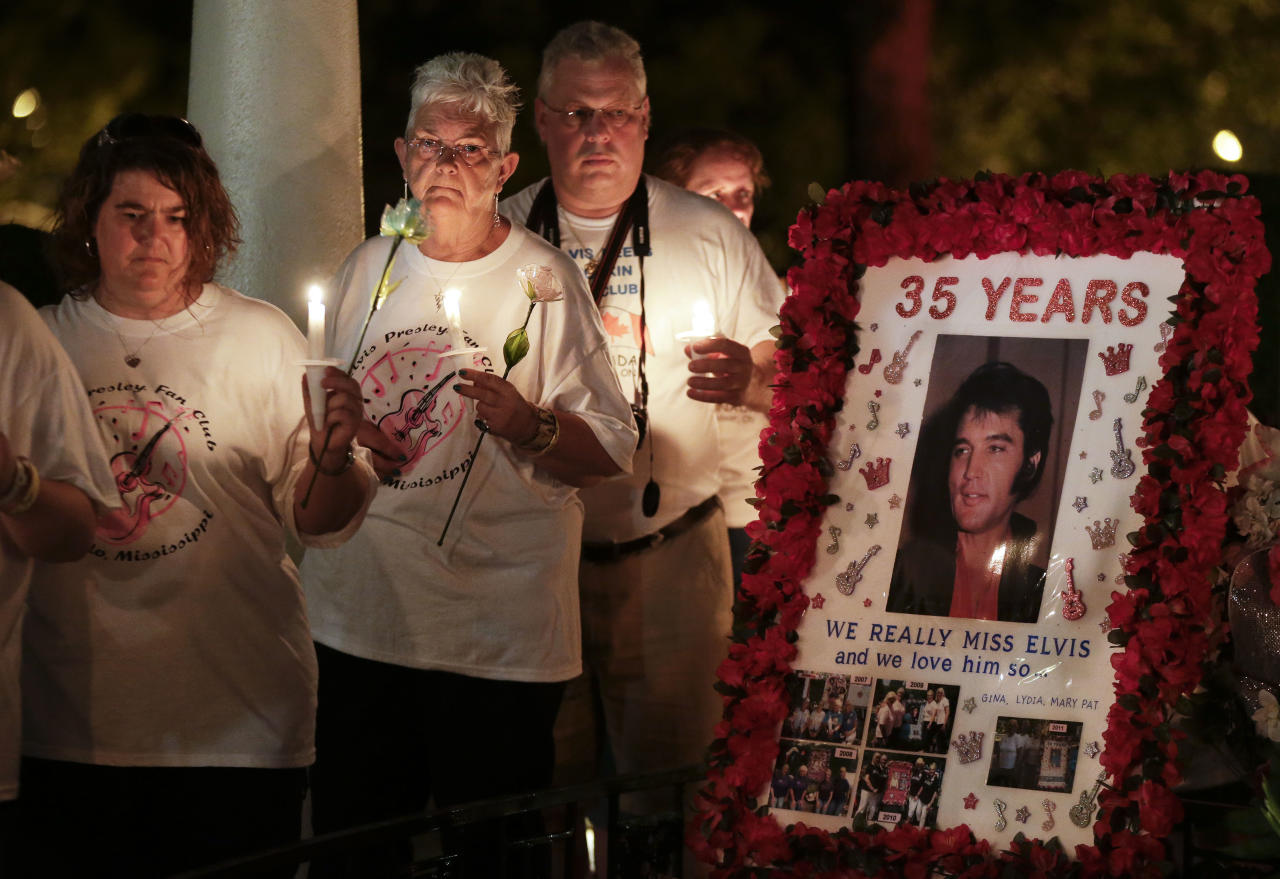 Elvis Presley fans walk past his grave during a candlelight vigil at Graceland, Presley's Memphis, Tenn. home, on Wednesday, Aug. 15, 2012. Fans from around the world are at Graceland to commemorate the 35th anniversary of Presley's death. (AP Photo/Mark Humphrey)