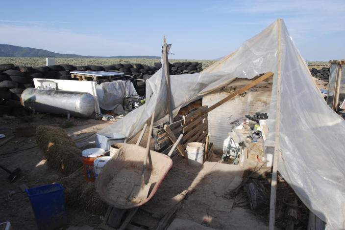 Various items litter a squalid makeshift living compound in Amalia, N.M., on Friday, Aug. 10, 2018, where five adults were arrested on child abuse charges and remains of a boy were found. The remains, which haven't been positively identified, may resolve the fate of Abdul-ghani Wahhaj, a missing, severely disabled Georgia boy. Eleven other children were found at the compound during a raid last week. (AP Photo/Morgan Lee)