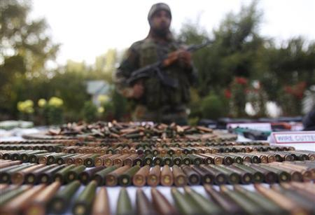 An Indian army soldier stands behind a display of seized arms and ammunition at a garrison in Srinagar, October 7, 2013. REUTERS/Danish Ismail