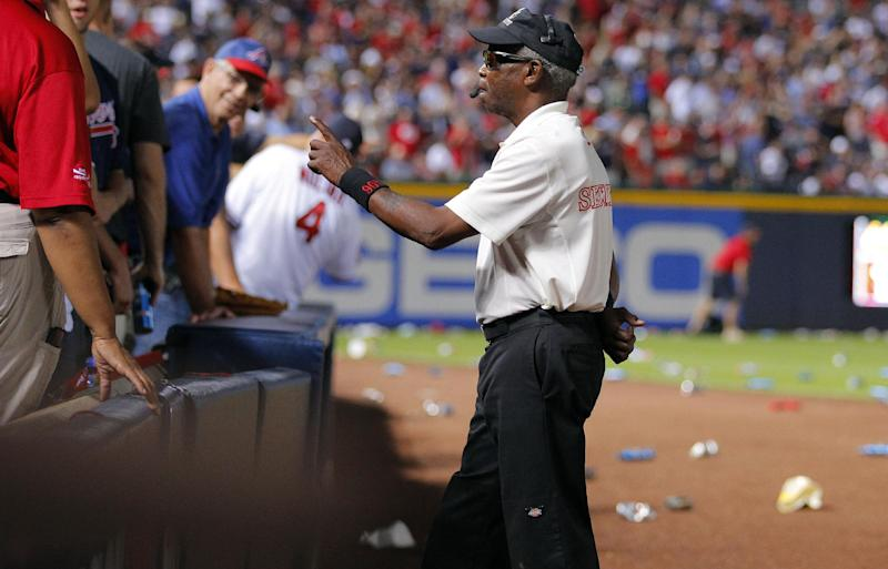 A security official shouts to fans to not throw trash on the field during the eighth inning of the National League wild card playoff baseball game between the Atlanta Braves and the St. Louis Cardinals, Friday, Oct. 5, 2012, in Atlanta. The Cardinals won baseball's first wild-card playoff, taking advantage of a disputed infield fly call that led to a protest and fans littering the field with debris to defeat the Braves 6-3. (AP Photo/Todd Kirkland)