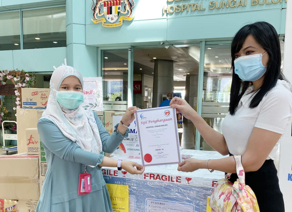 Malaysian sugar baby, Natalie, 28, handed over the items to Dr Ainul Husna at the Sungai Buloh Hospital including 10 portable air-conditioners which the hospital was in dire need of. — Picture courtesy of Sugarbook
