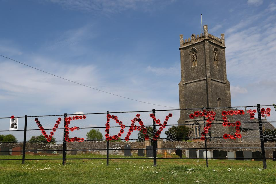 BINEGAR, ENGLAND - MAY 08: A portrait of Robinson Collins is displayed outside Holy Trinity Church to commemorate VE Day on May 08, 2020 in Binegar, Somerset, United Kingdom. The UK commemorates the 75th Anniversary of Victory in Europe Day (VE Day) with a pared-back rota of events due to the coronavirus lockdown. On May 8th, 1945 the Allied Forces of World War II celebrated the formal acceptance of surrender of Nazi Germany. (Photo by Michael Steele/Getty Images)