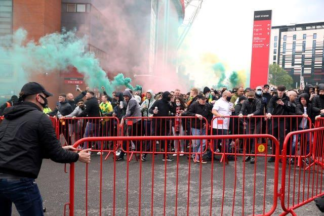 Fans move barriers outside the ground as they let off flares