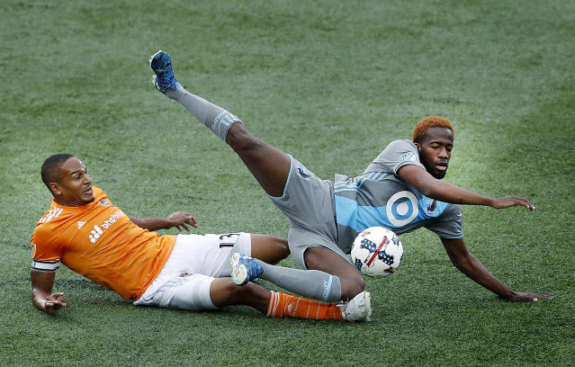 Houston Dynamo's Ricardo Clark (13) and Minnesota United's Kevin Molino vie for the ball during the first half of an MLS soccer match Wednesday, June 19, 2017, in Minneapolis. (Carlos Gonzalez/Star Tribune via AP)