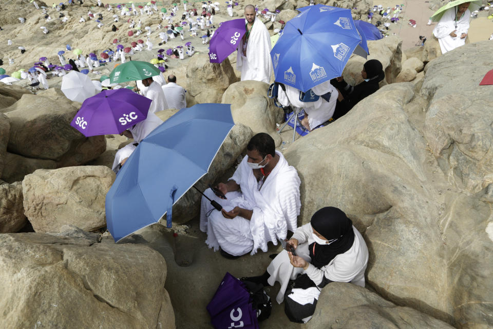 A Muslim pilgrim couple prays on the rocky hill known as the Mountain of Mercy on the Plain of Arafat during the annual hajj pilgrimage, near the holy city of Mecca, Saudi Arabia, Monday, July 19, 2021. The coronavirus has taken its toll on the hajj for a second year running. What once drew some 2.5 million Muslims from all walks of life from across the globe, the hajj pilgrimage is now almost unrecognizable in scale. (AP Photo/Amr Nabil)