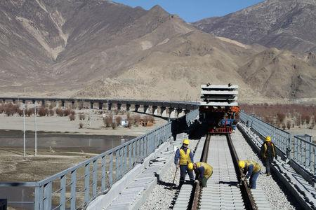 Workers are seen on railway tracks at a bridge over Yarlung Tsangpo river as they work on the construction of the railroad linking Lhasa and Nyingchi