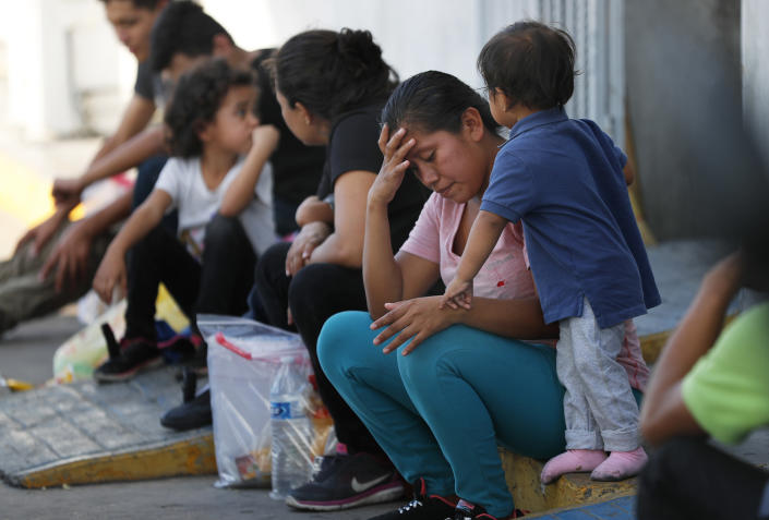 Migrants wait at an immigration center on the International Bridge 1, in Nuevo Laredo, Mexico, Tuesday, July 16, 2019. A U.S. policy to make asylum seekers wait in Mexico while their cases wind through clogged U.S. immigration courts has also expanded to the violent city of Nuevo Laredo. (AP Photo/Marco Ugarte)