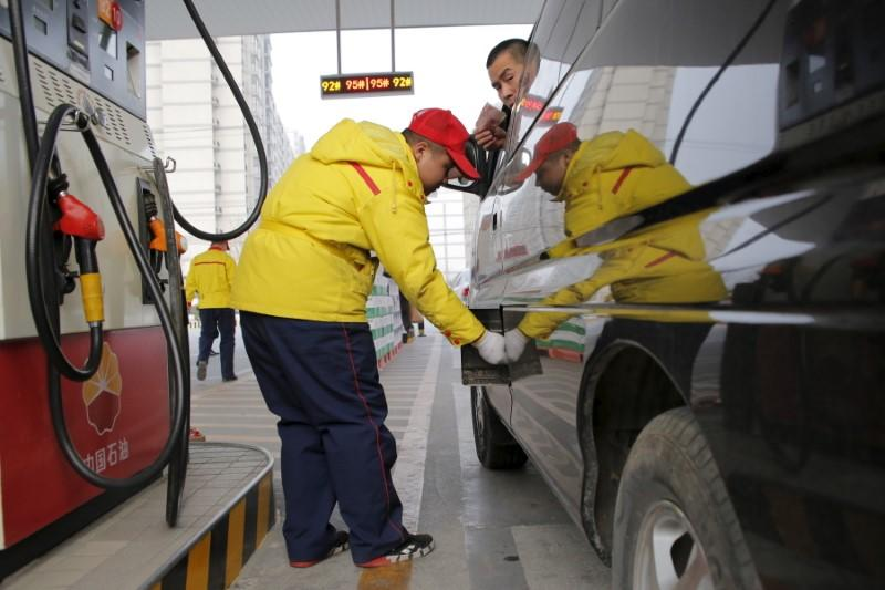 A gas station attendant pumps fuel into a customer's car at PetroChina's petrol station in Beijing