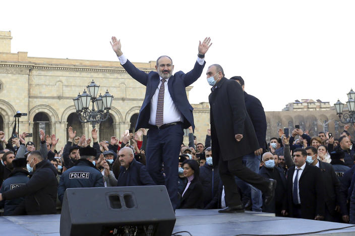 Armenian Prime Minister Nikol Pashinyan greets his supporters during a rally in the central in Yerevan, Armenia, Thursday, Feb. 25, 2021. Armenia's prime minister accused top military officers on Thursday of attempting a coup after they demanded he step down, adding fuel to months long protests calling for his resignation following the nation's defeat in a conflict with Azerbaijan over the Nagorno-Karabakh region. (Stepan Poghosyan/PHOTOLURE via AP)